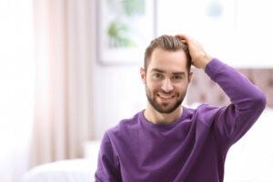 גבר נוגע בשיער עם חולצה סגולה ומחייך