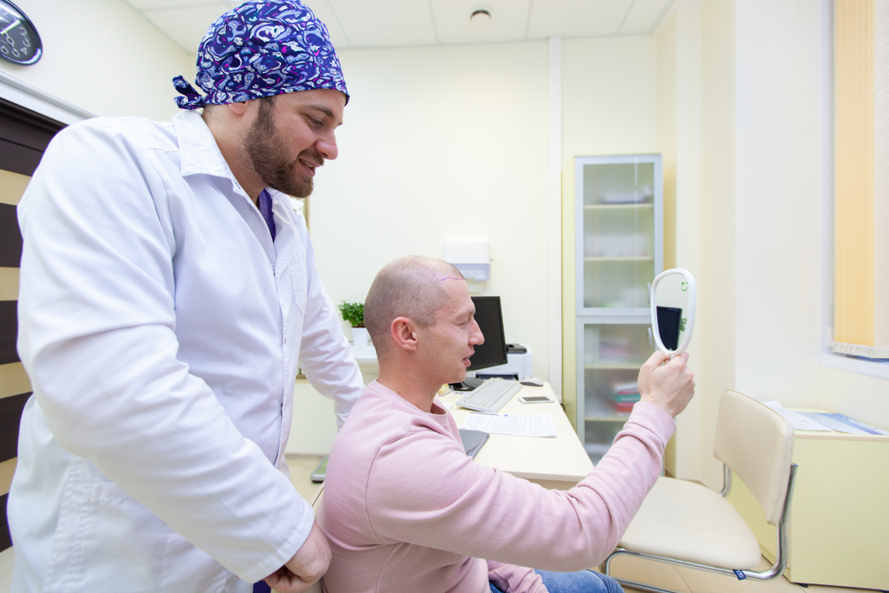 השתלת שיער בחול המטופל מחזיק מראה לאחר ההשתלה
