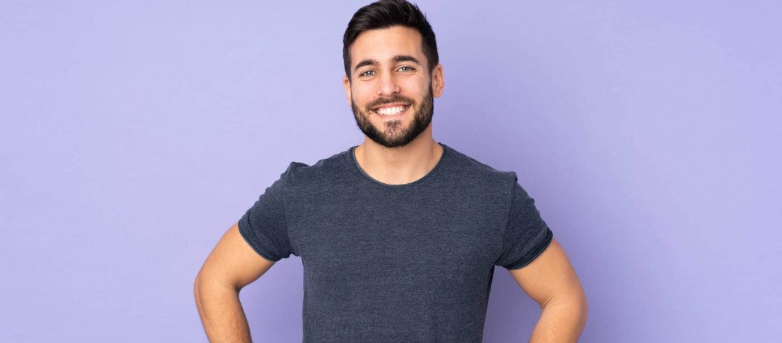 caucasian-handsome-man-posing-with-arms-hip-smiling-isolated-purple-wall_optimized